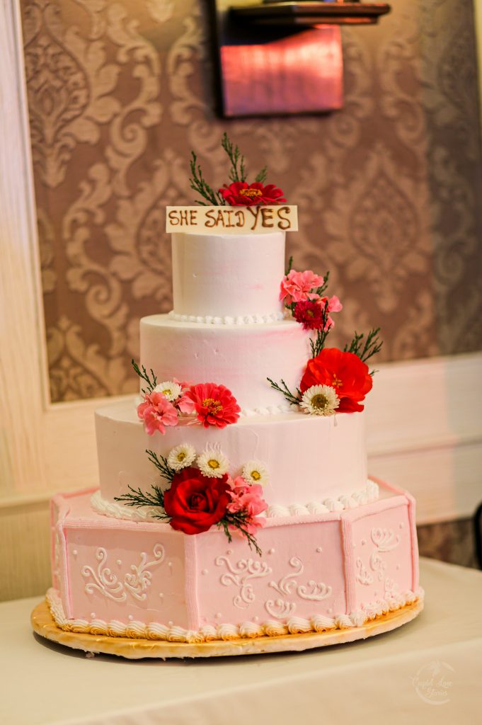 Aparna & Arnav's Pastel Peach Colored Floral Wedding Cake with a 'She Said Yes' Cake Topper