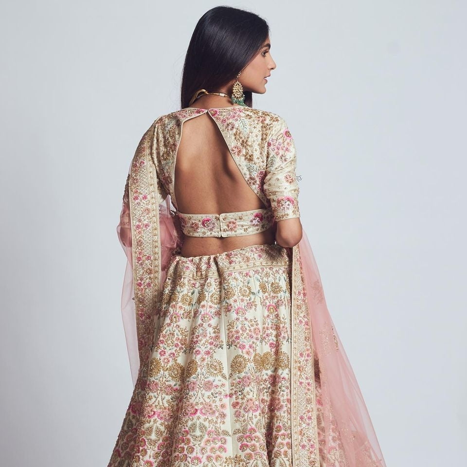 Backless blouse design for lehenga with pastel embroidery
