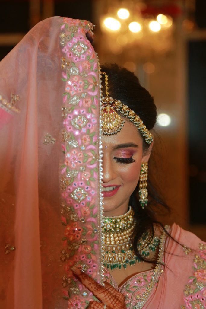 floral embroidered pink bridal veil with bride in heavy jewellery and makeup