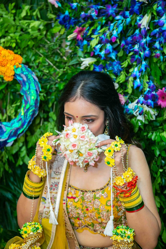 bride wearing face mask made of flowers for haldi ceremony
