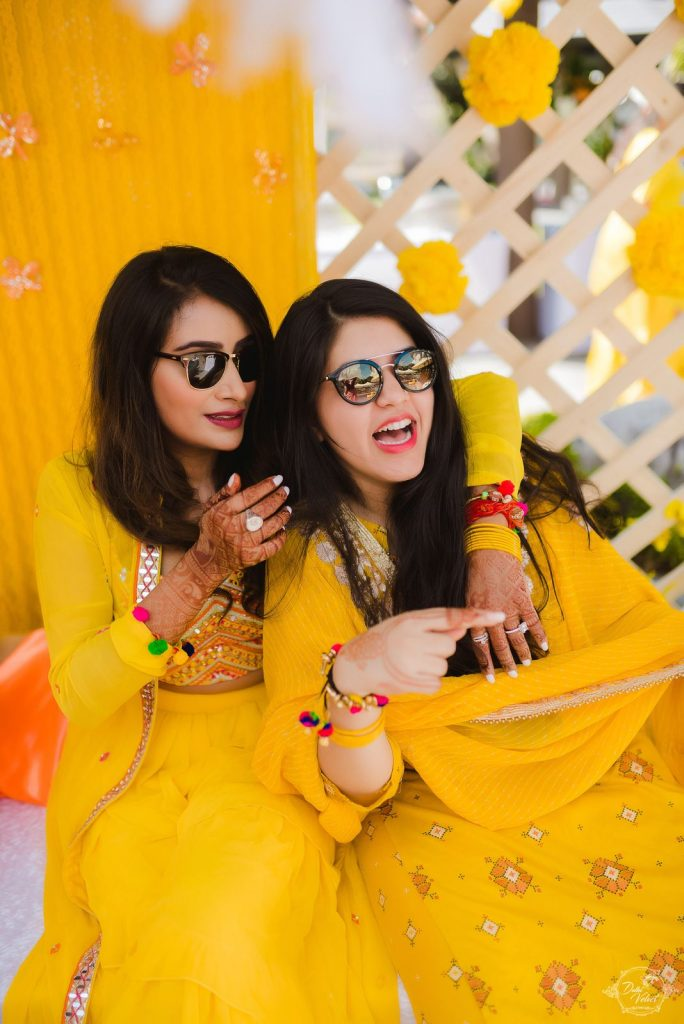 Nikita's picture with her bridesmaid in coordinating yellow outfits for a sunrise yellow theme haldi ceremony