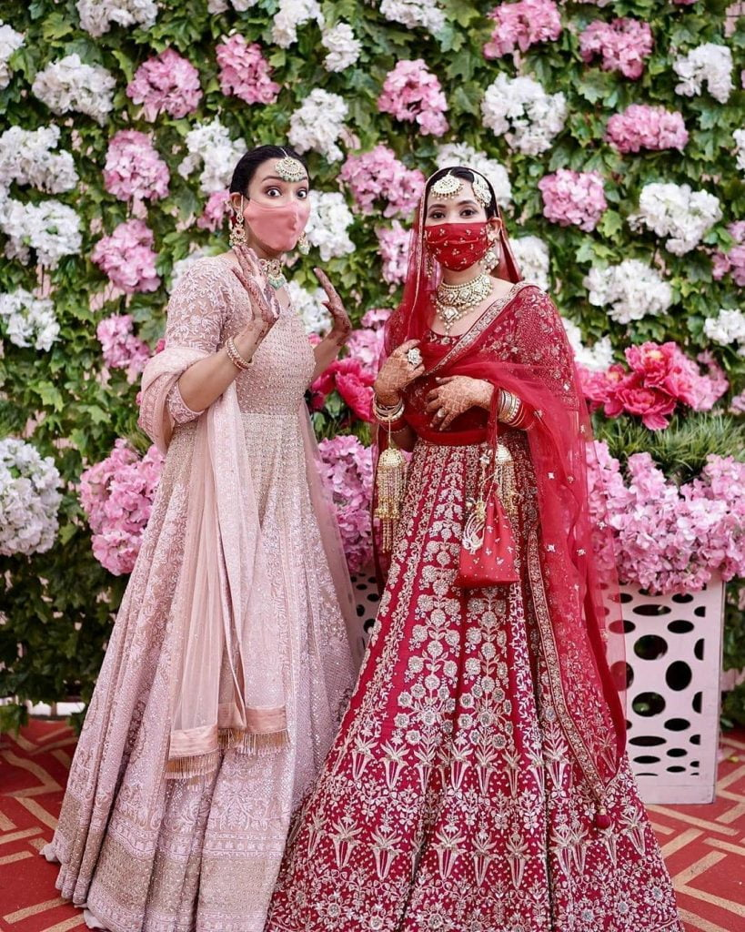 outfit coordinated masks with bride and bridesmaid in pastel and traditional red lehengas