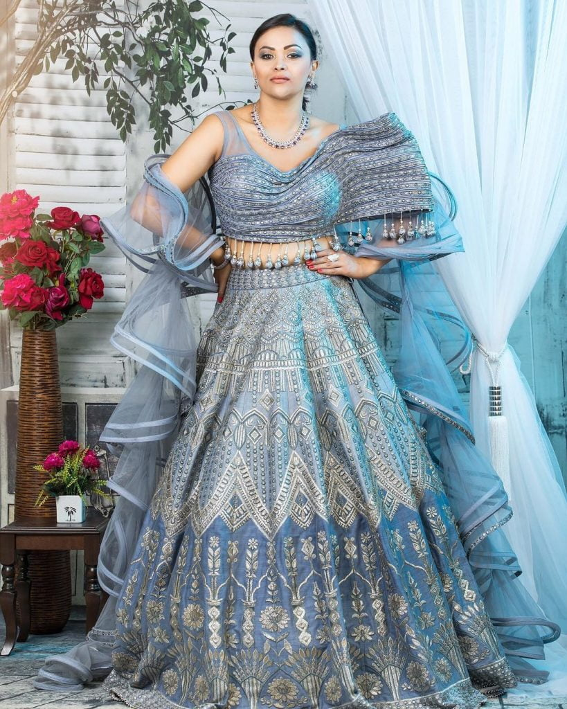 Pastel blue lehenga with an asymmetric blouse and tassel details