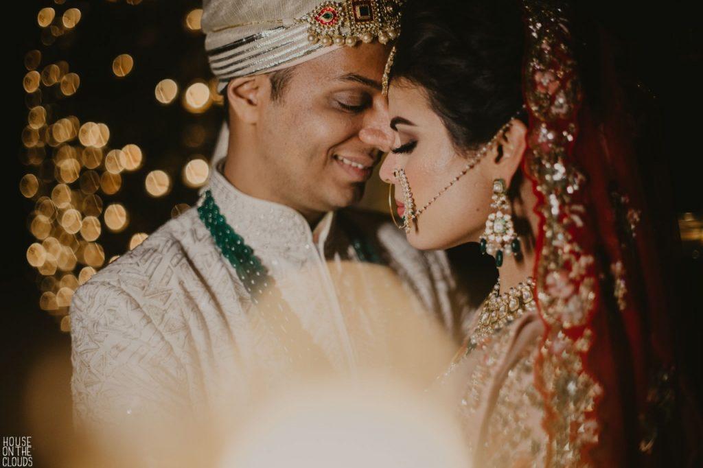 Palak & Pankaj posing for a romantic shot in designer bridal dresses at their Ananata Udaipur Wedding