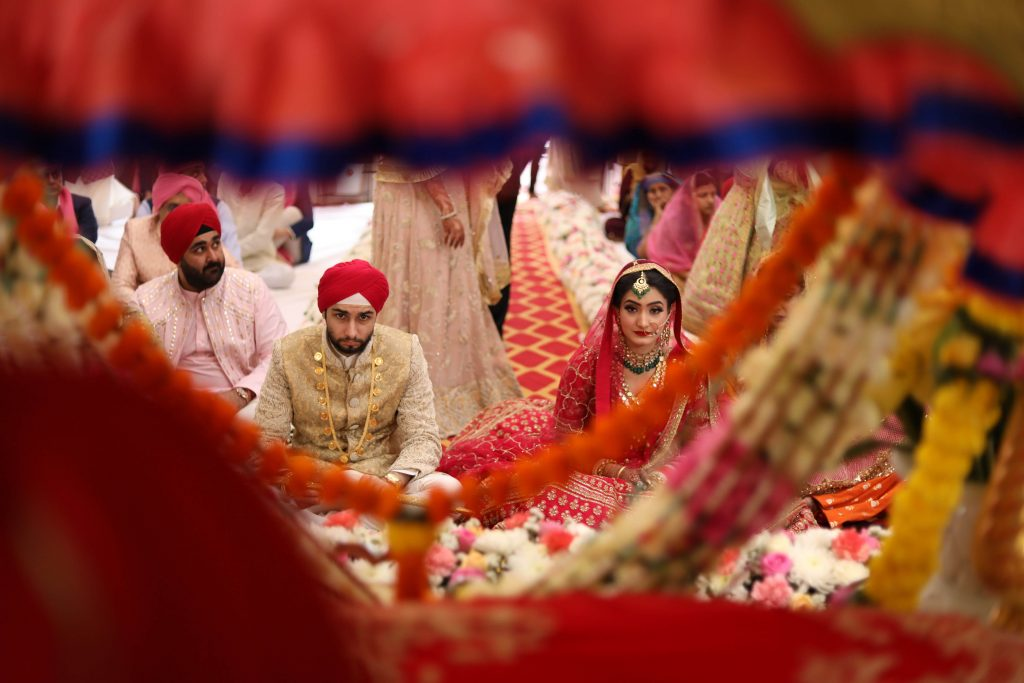 The auspicious wedding ceremony being held at a gurudwara alon with newly wedded in their color coordinated outfits.
