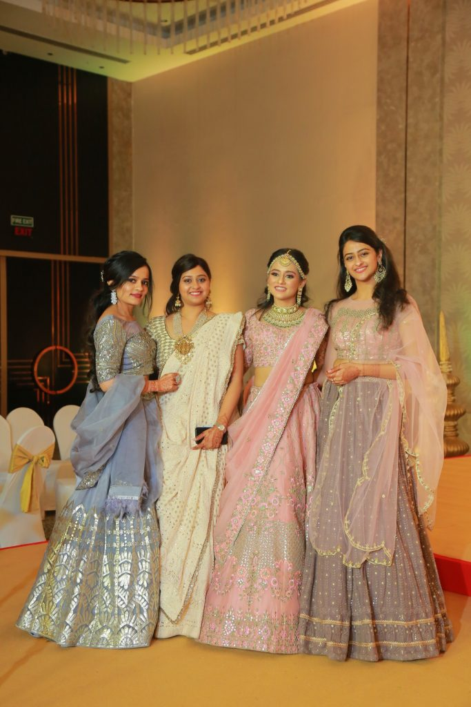 bride and bridesmaids in offbeat lehengas for wedding reception