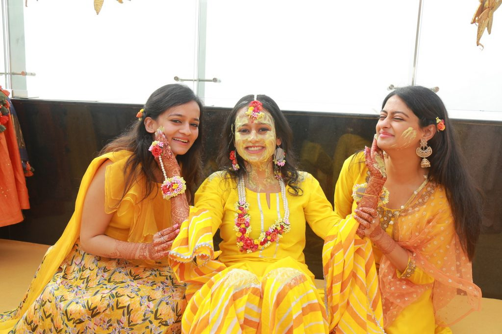 bridesmaid and bride in yellow kurta and multicolour flower jewellery