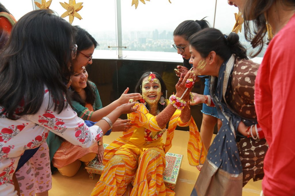 candid of bride and family laughing in fun haldi ceremony