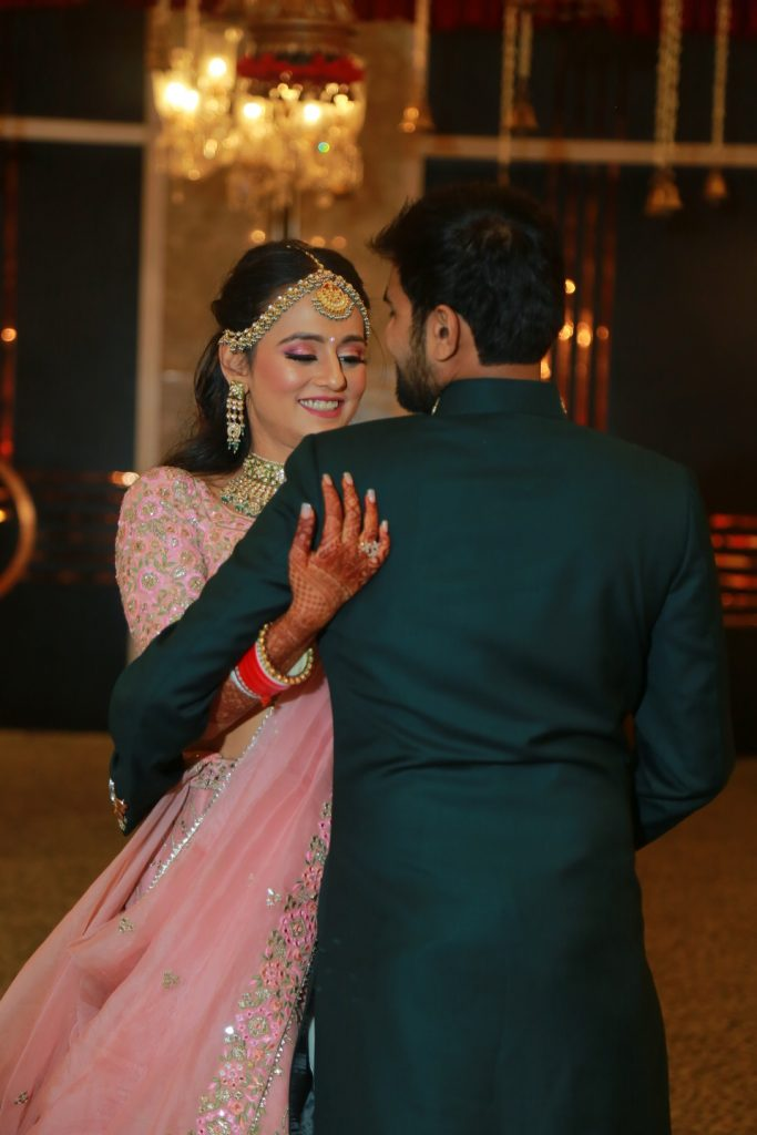 indian bride posing with groom in dark green kurta for reception