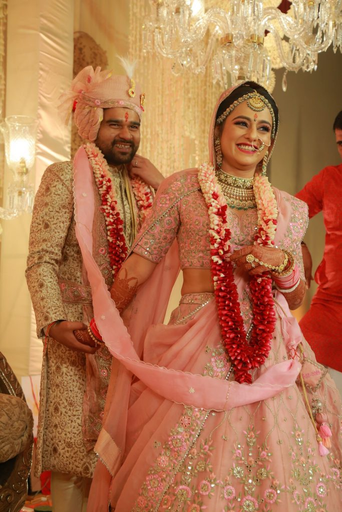 bride and groom in matching light pink attire during phera ceremony