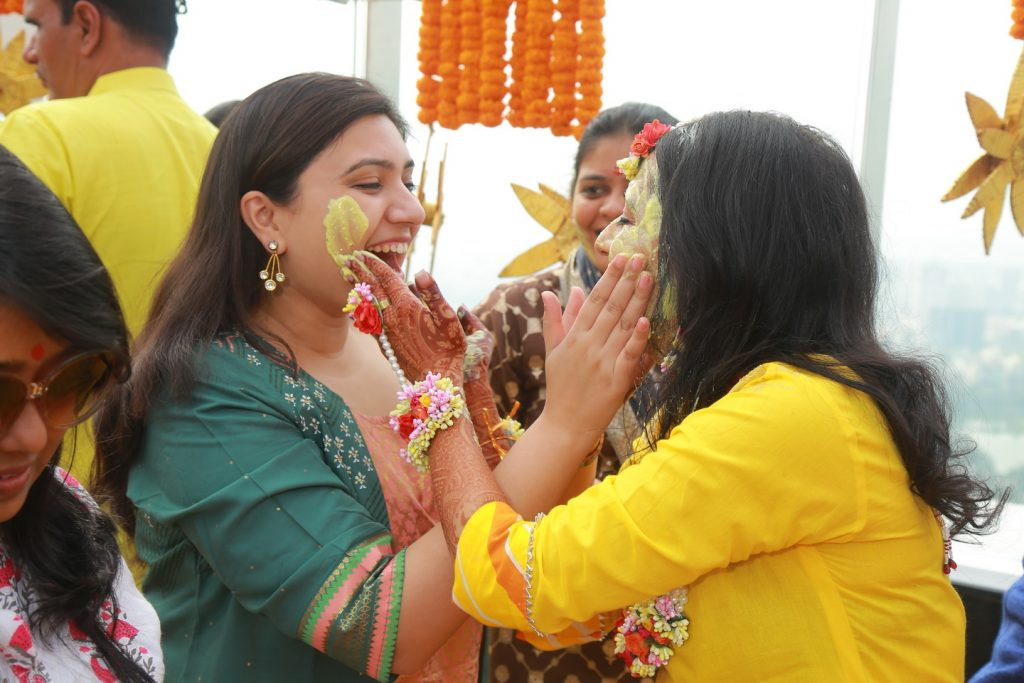 candid of bride applying mehendi to bridesmaid in haldi function