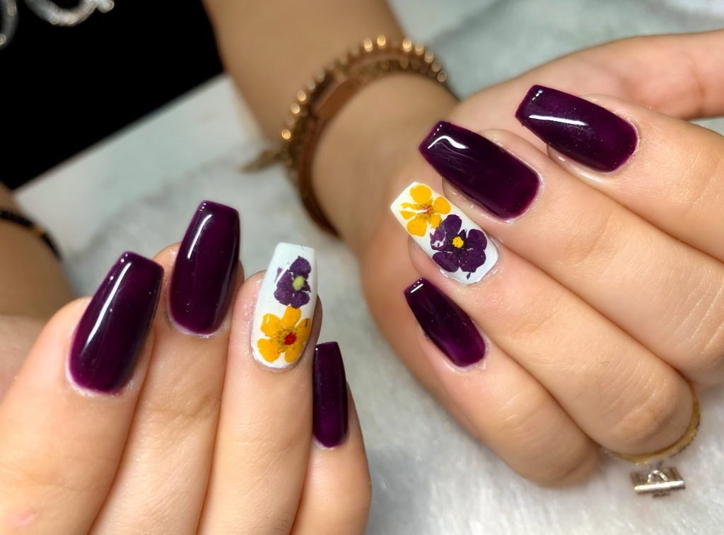 dark purple bold nails with white nails and yellow purple flower print