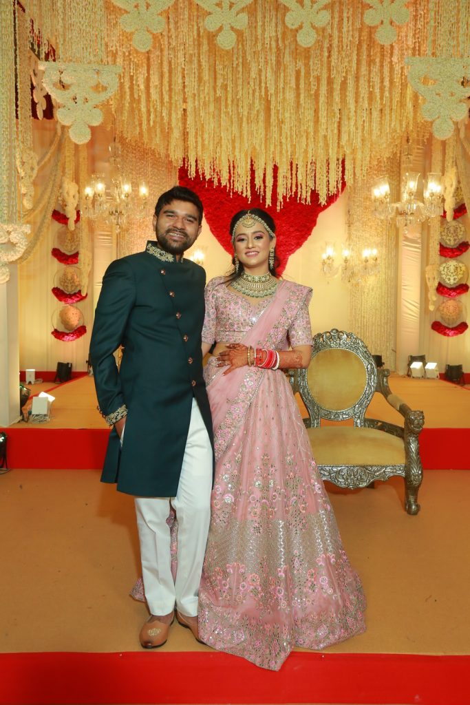 portrait of bride in pink lehenga and groom in dark kurta for reception