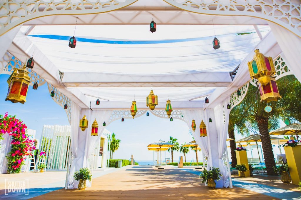 glass lamps and white outdoor tent for poolside moroccan mehendi decoration by Ferns and Petals Weddings