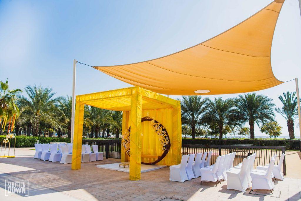 beach wedding in dubai haldi floral yellow ceremony stage