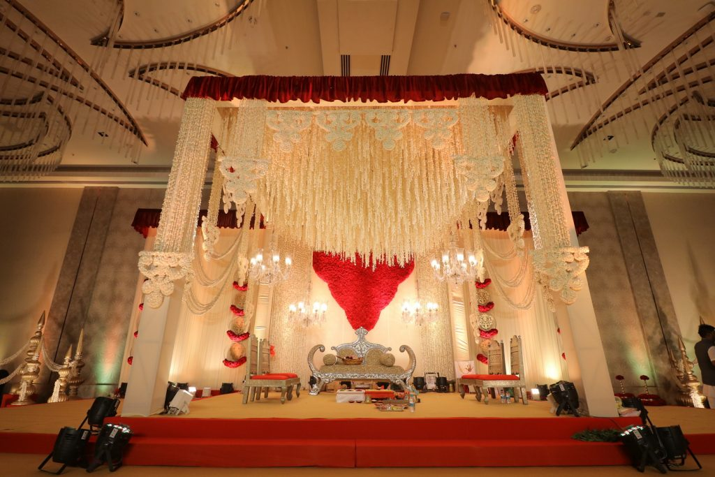indian wedding mandap with red drapes and white floral mandap