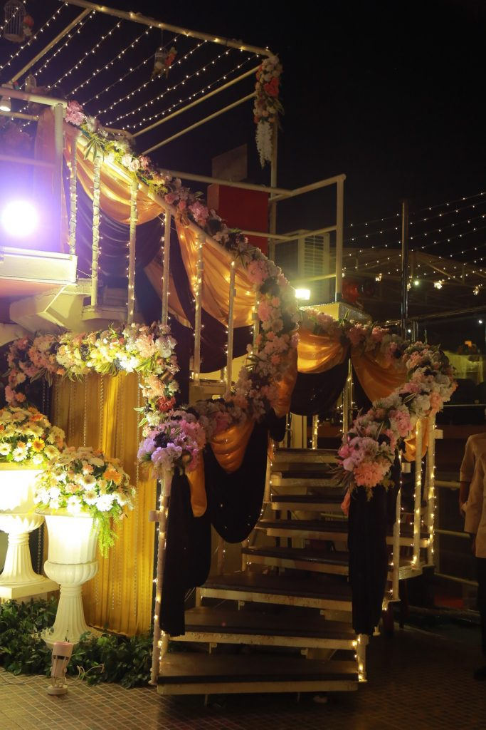 white flowers and golden red drapes on staircase for sangeet
