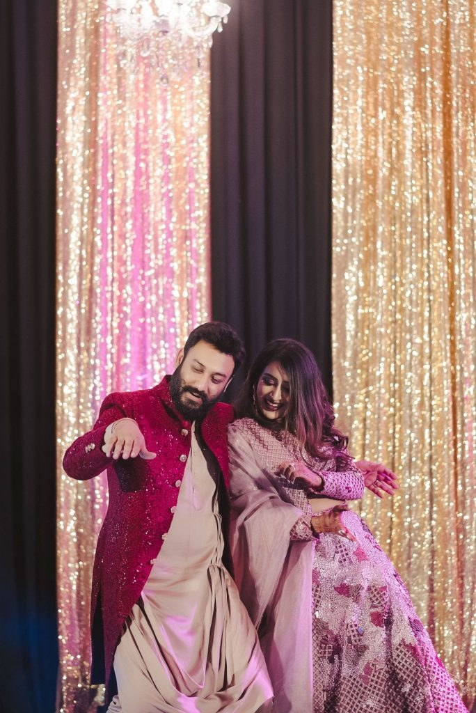 fun couple dancing in musical sangeet in coordinated outfits