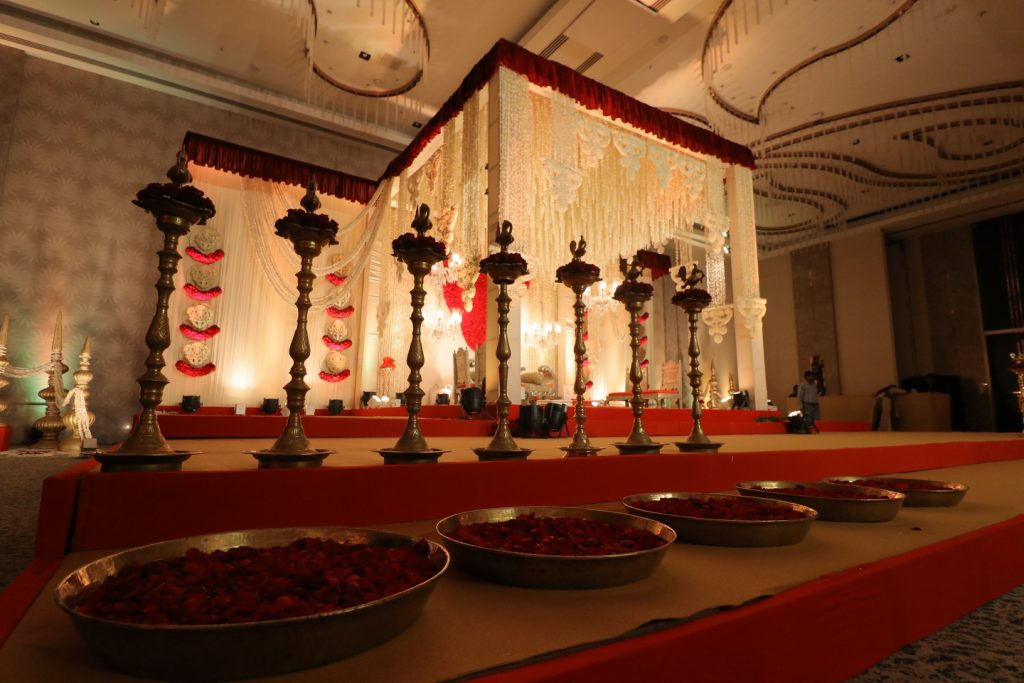 indian wedding mandap with roses and golden accessories