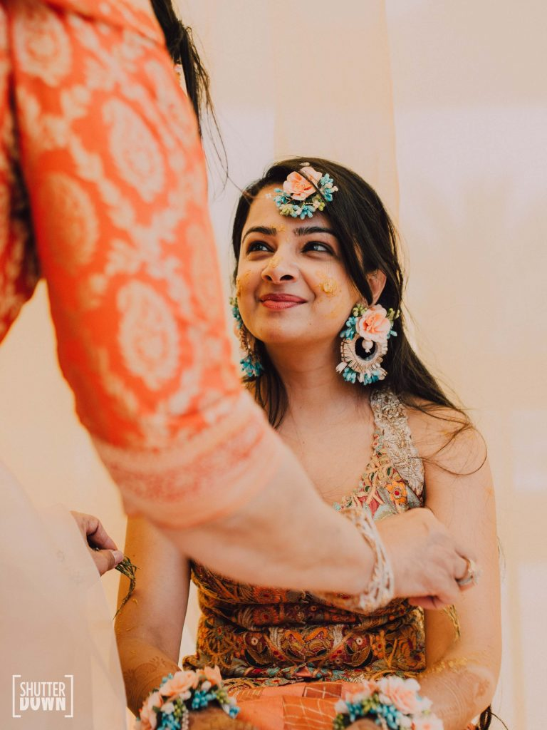 Candid Portrait of Mrighna in shades of sunrise themed haldi ceremony for her beach wedding in Dubai