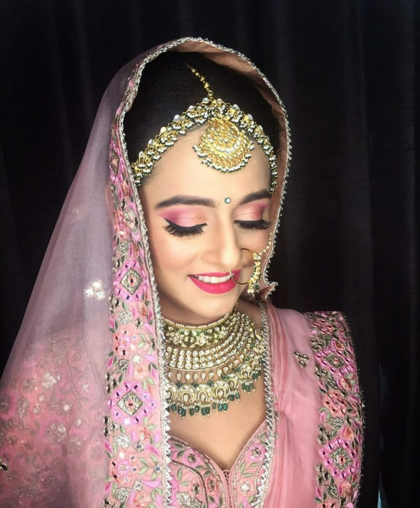 indian bride in onion pink lehenga, light makeup and golden green jewellery