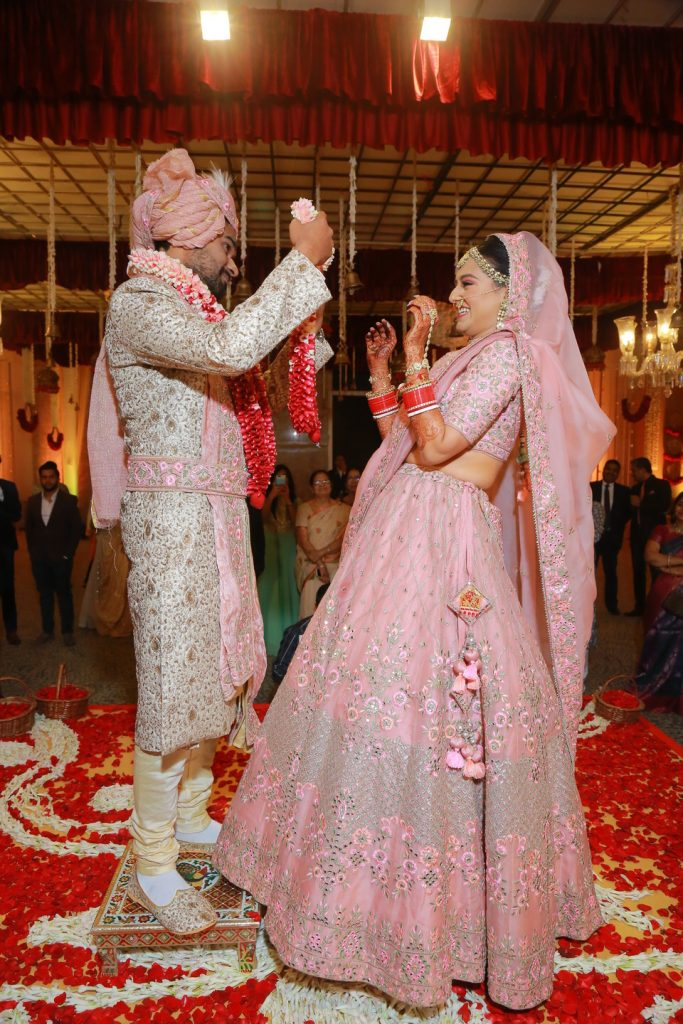 groom in white sherwani with bride in pink lehenga puting varmala