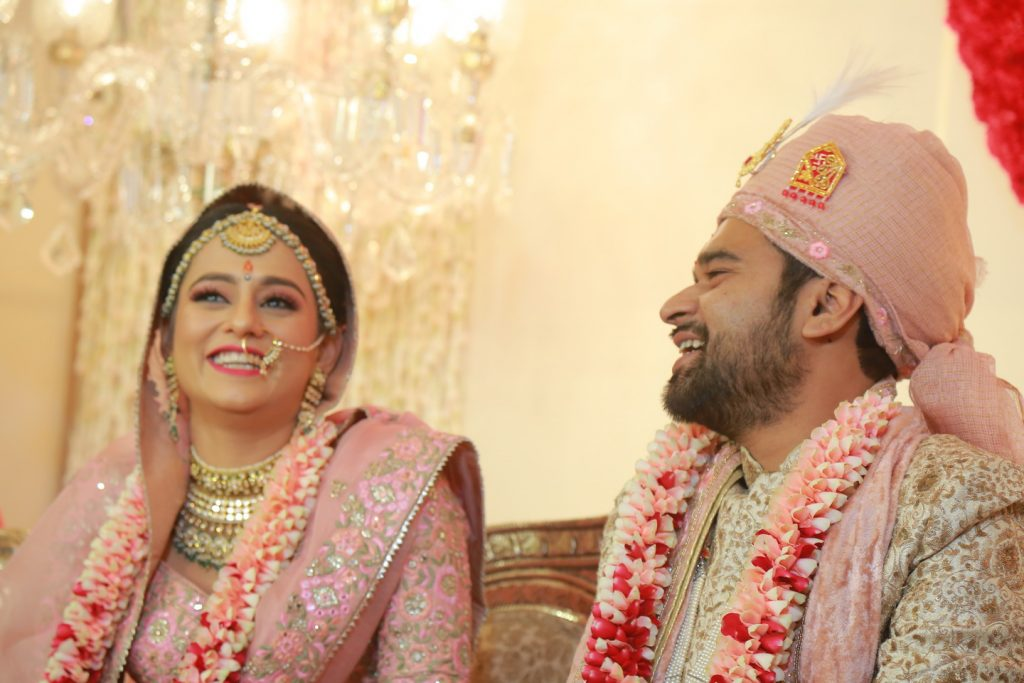 candid of indian bride and groom in their matching pink and white attire