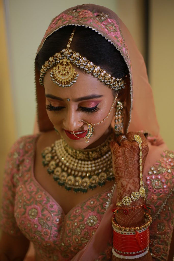 indian bride in onion pink lehenga, light makeup and jewellery