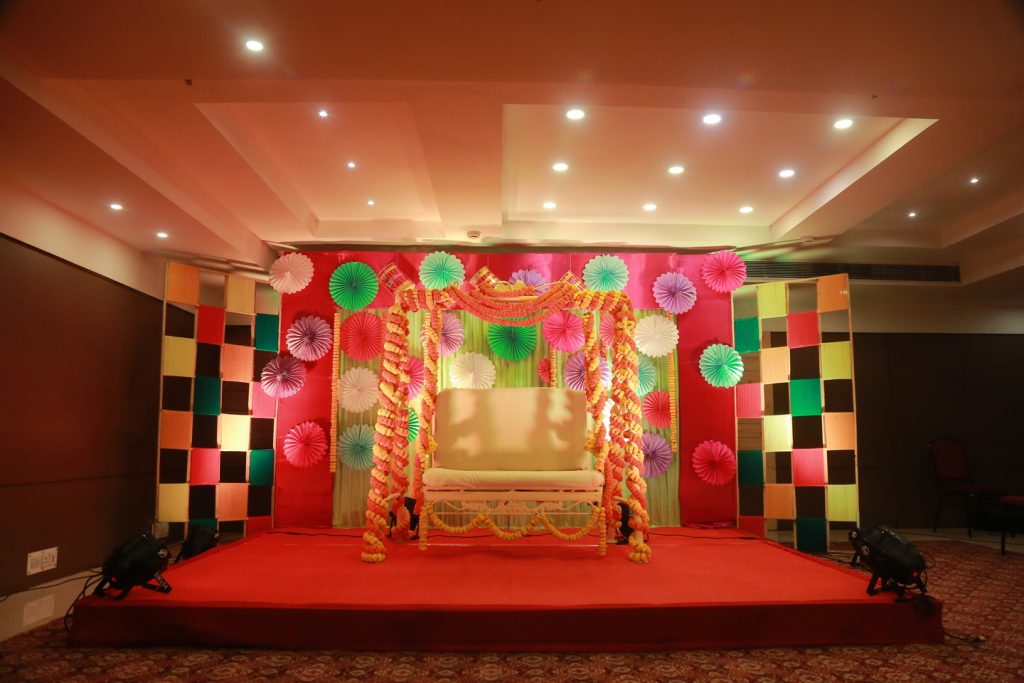 bengali marwari mehendi venue with marigold flower chair and paper decorations