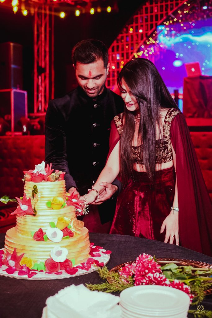 Candid of couple cutting three tier cake for pre wedding reception