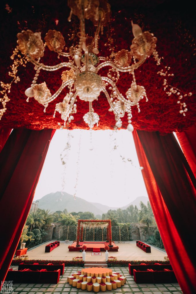golden chandelier and red themed open stage decoration for haldi