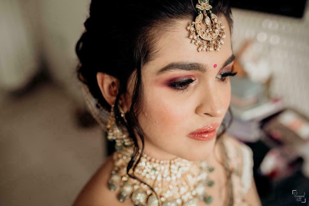 Indian bride in rosewood pink smokey eye makeup and glossy nude lipstick