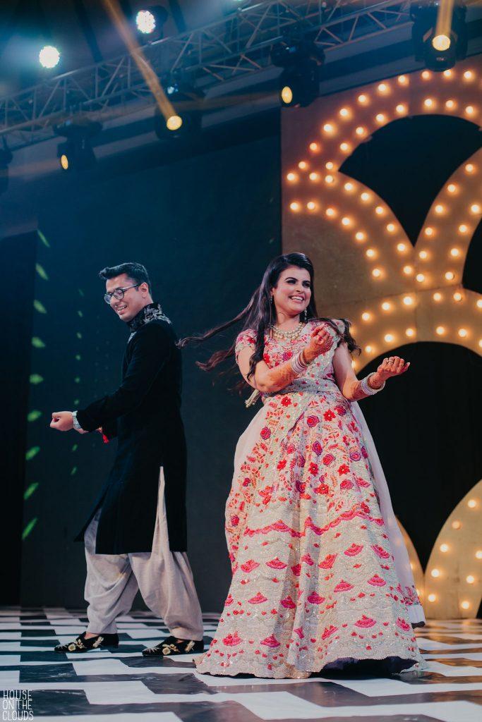 Fun Couple Sangeet Candid Dancing Portrait Photography In Bridal Designer Wear