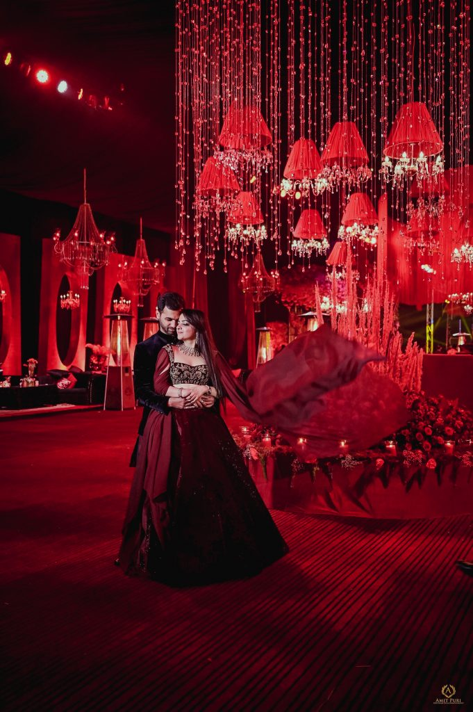 red themed wedding reception photoshoot in velvet red Manish Malhotra designer dress