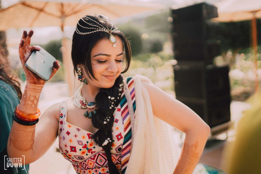 white embroidered lehenga by Tarun Tahiliani and jewelled head chain by Maya Sanghvi
