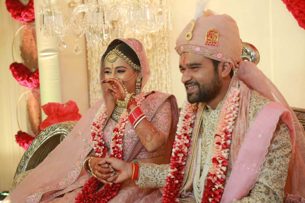 candid portrait of bride in coordinated pink lehenga and groom in pink sehra