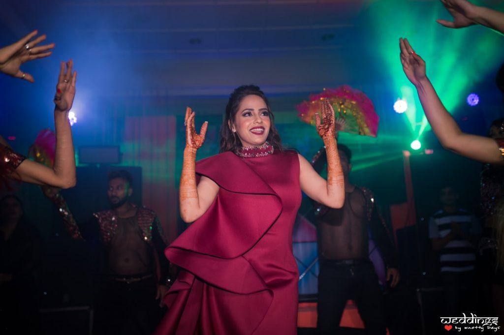 Shalini enjoying her cocktail night in her ruffled maroon dress before her Dusit Thani Hua Hin Wedding