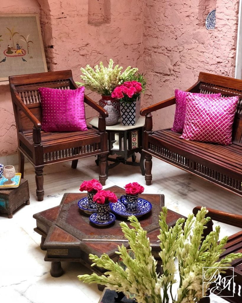 bright pink pillow covers on brown benches for wedding decoration