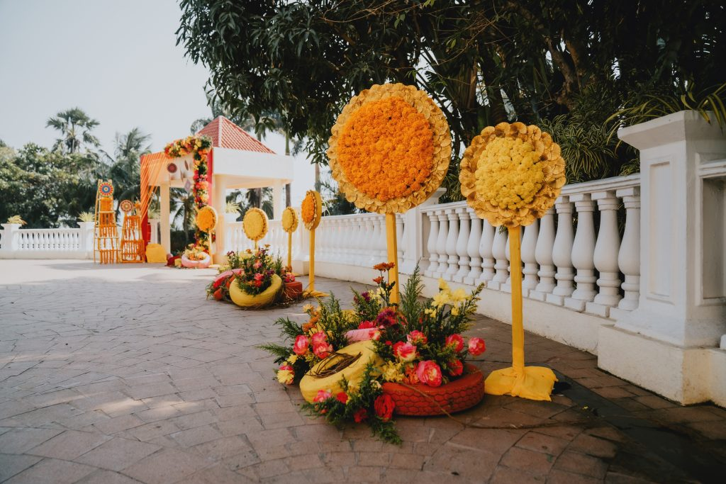 yellow and red rustic painted DIY tyres decor with flower bushes for wedding