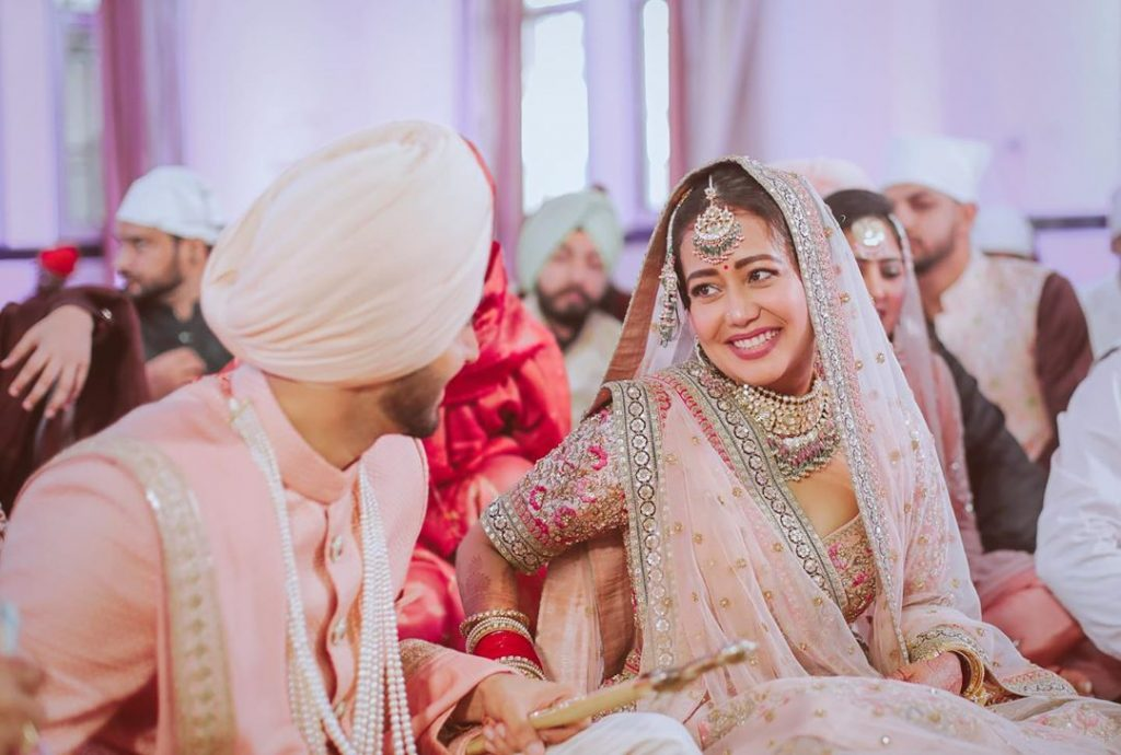 Neha kakkar in a pastel pink sabyasachi lehenga and rohanpreet in a matching pastel pink sherwani for their anand karaj wedding ceremony in delhi