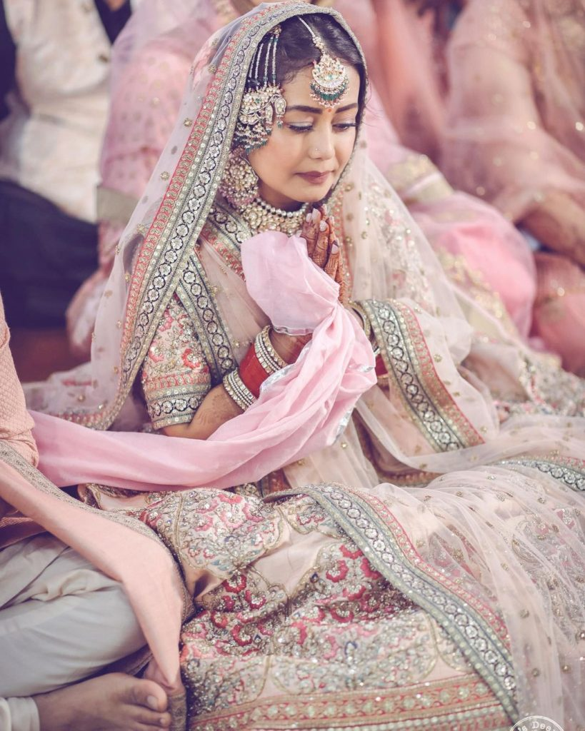 Neha Kakkar's Beautiful Shot in a Sabyasachi Pastel pink lehenga, red chooda and kundan jewellery with a passa for her traditional punjabi anand karaj wedding ceremony