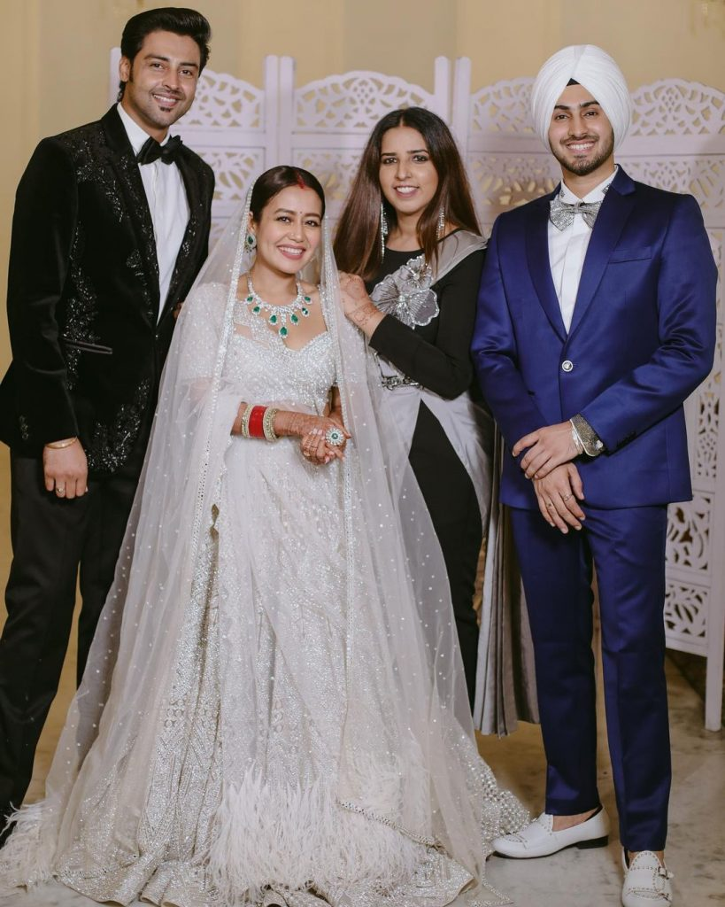 Neha Kakkar and Rohanpreet Singh posing with their guests in their wedding reception