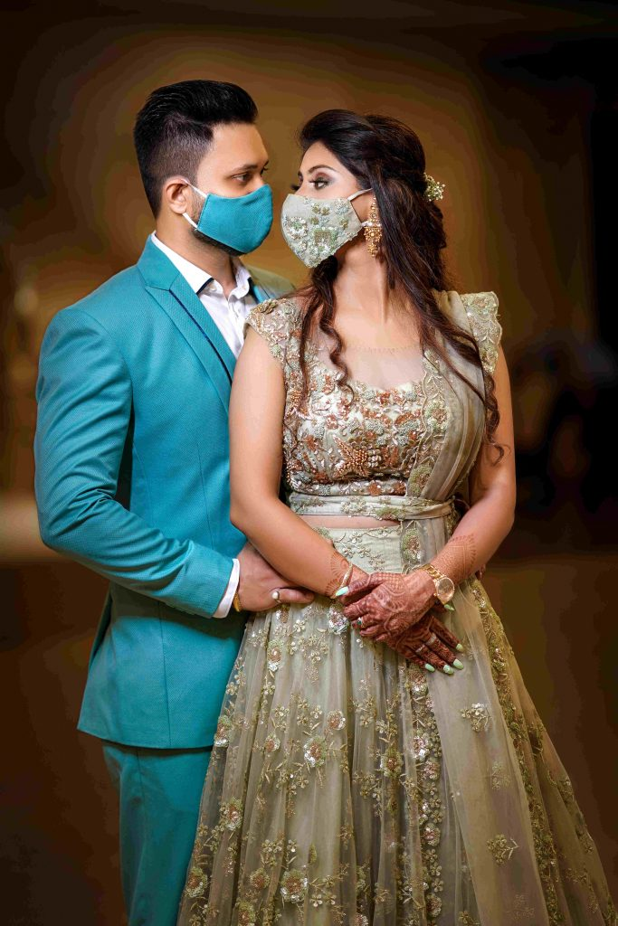 Bride and Groom in blue & olive green wedding face masks coordinated with their respective outfits