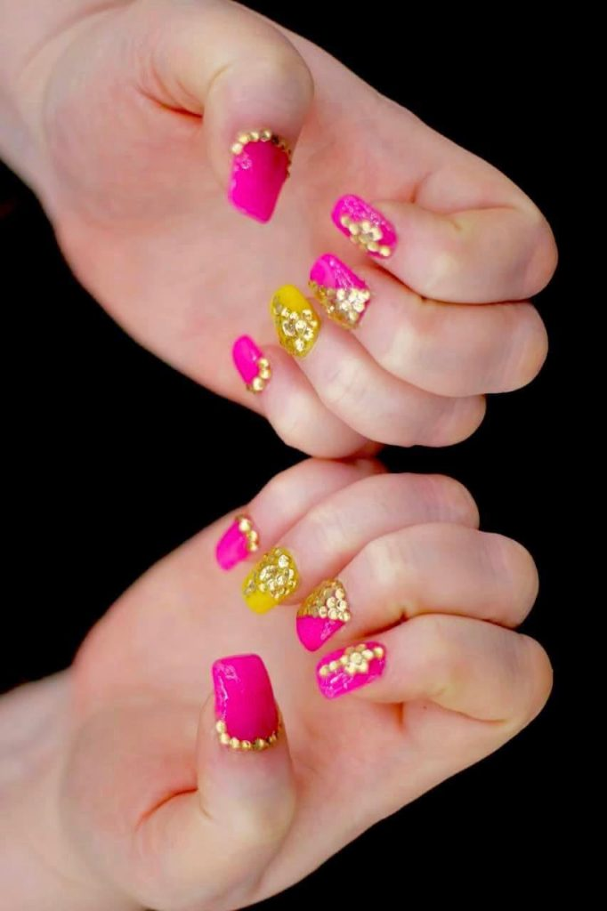 bright hot pink nails with golden jewels