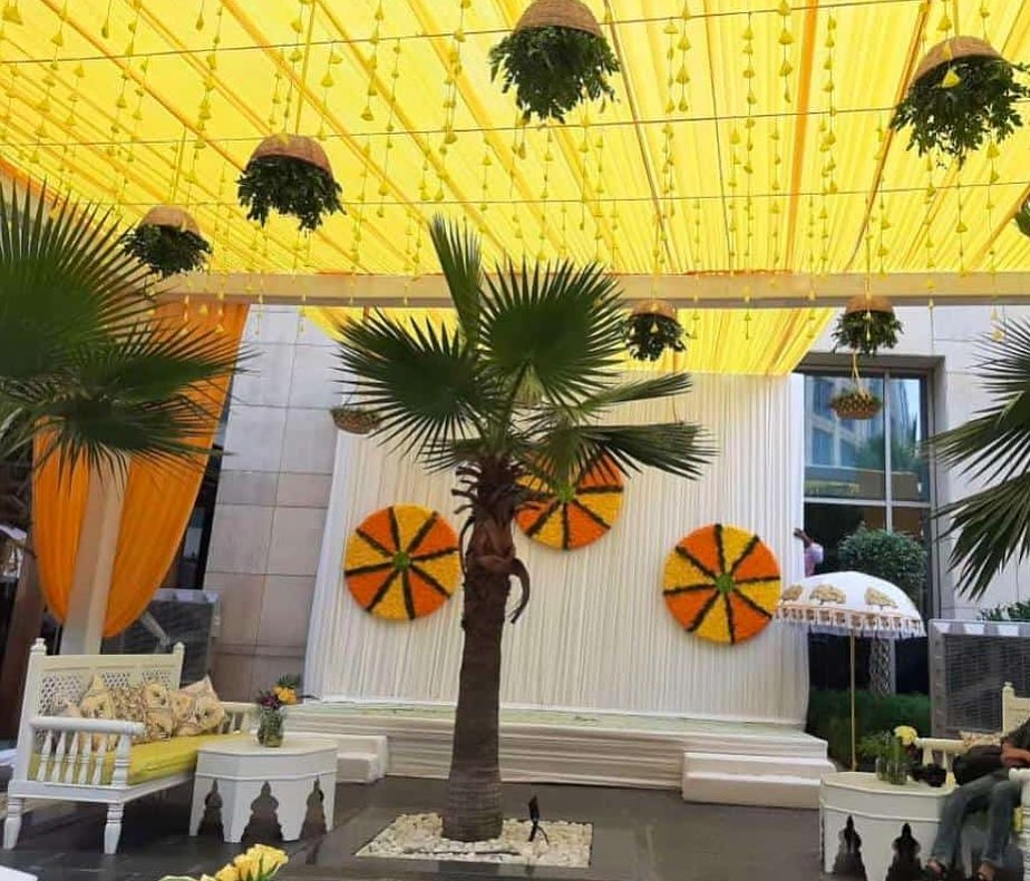 haldi ceremony venue with yellow marigold wheel backdrop theme neha kakkar