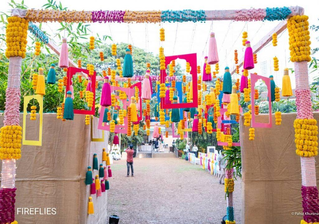 colorful hanging DIY tassel, frames and marigold wedding decor