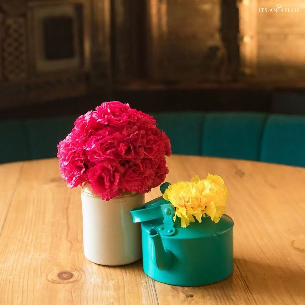 blue kettle with dainty yellow flowers and mason jar with pink roses