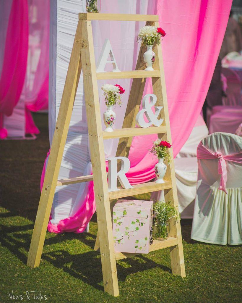 beige ladder wedding decor with flower vases
