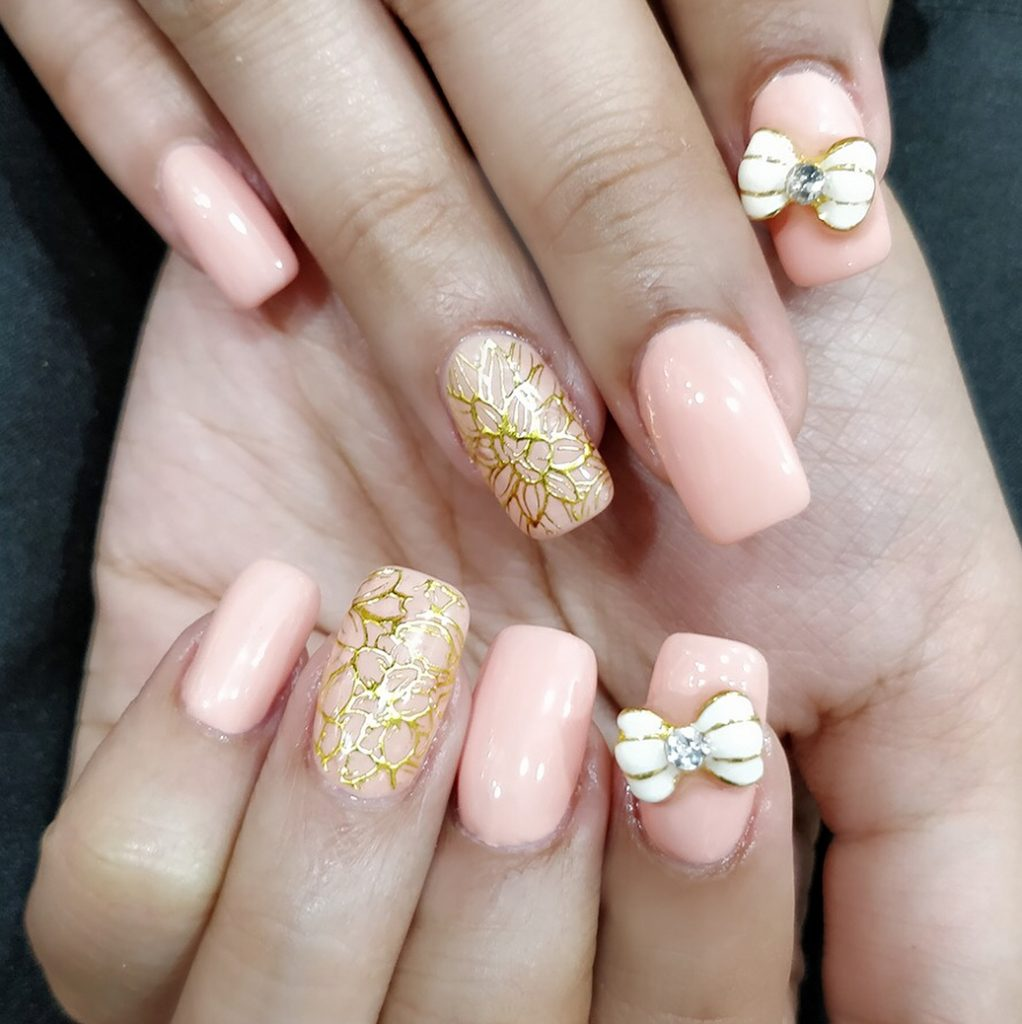 baby pink square nails with 3d nail bow accessory and golden floral details