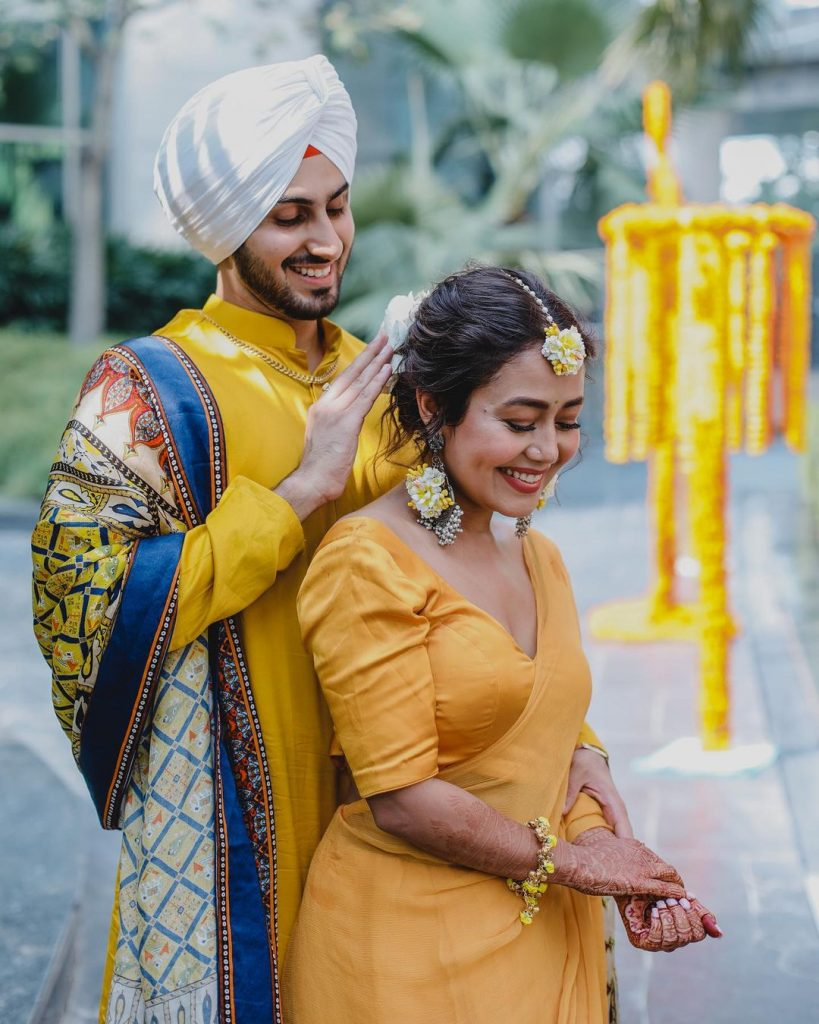 bride neha and groom rohanpreet in coordinating yellow outfits posing for haldi photography